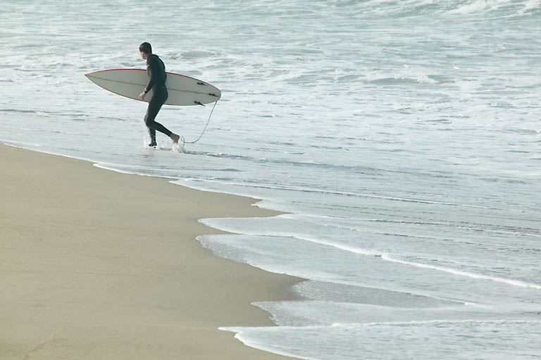surfer walking beach uid 1427678.jpg